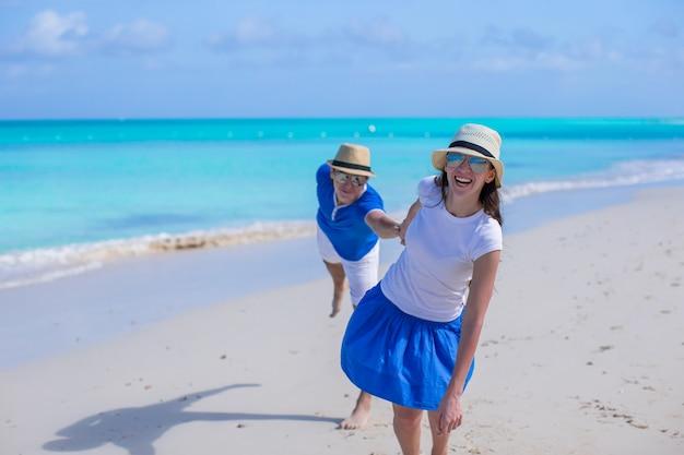 幸せなカップルは、カリブ海のビーチでの休暇中に楽しい時を過す Premium写真