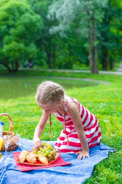 湖の近くの屋外のピクニックにかわいい女の子 Premium写真