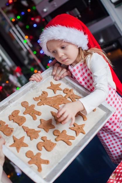 サンタの帽子の少女は彼女のクリスマスジンジャーブレッドクッキーを示しています Premium写真