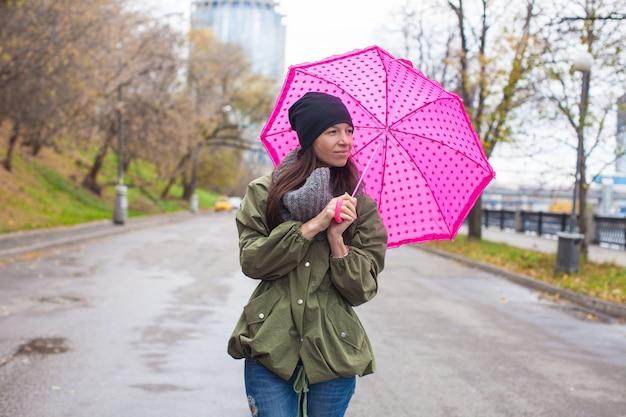 秋の雨の日に傘で歩く若い女性 Premium写真
