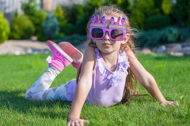 屋外笑顔幸せな誕生日のメガネのかわいい女の子 Premium写真