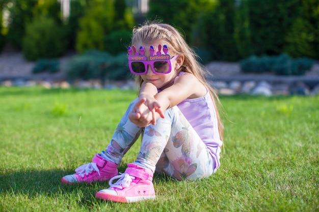 屋外笑顔幸せな誕生日の眼鏡の愛らしい少女 Premium写真
