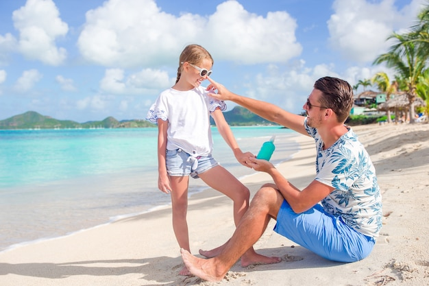 Молодой отец, применяя солнцезащитный крем для дочери нос на пляже. защита от солнца Premium Фотографии