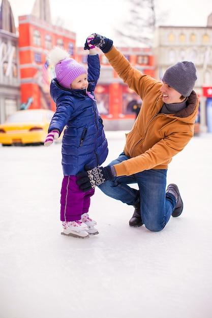 若い父親と幸せな少女は、スケートリンクで楽しい時を過す Premium写真
