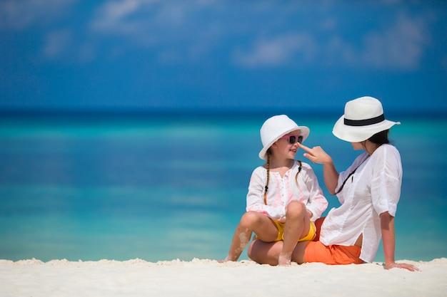 ビーチでの休暇中に小さな女の子と若い母親 Premium写真