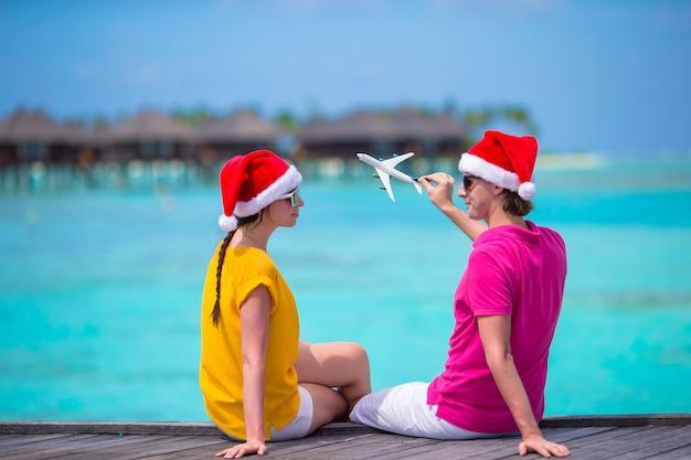 クリスマス休暇に木製の桟橋でリラックスしたサンタ帽子の若いカップル Premium写真