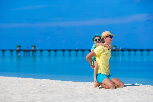 熱帯のビーチでの休暇中に小さな女の子と若い父 Premium写真