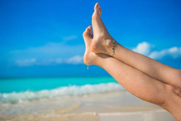 白い砂浜のビーチで女性の足のクローズアップ Premium写真