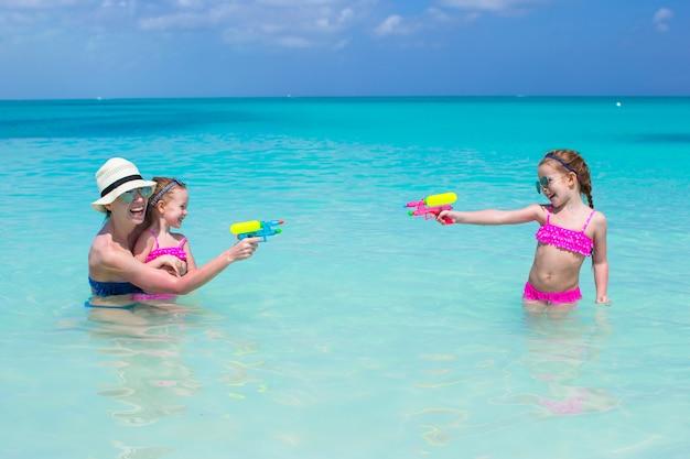 Счастливая семья на тропическом пляже, с удовольствием Premium Фотографии