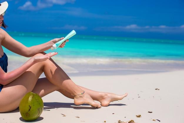 若い女性は、熱帯のビーチで彼女の滑らかな日焼けした足にクリームを適用します。 Premium写真