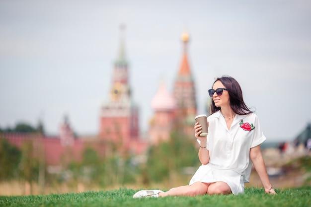 ヨーロッパの都市でコーヒーを飲んで幸せな若い都市女性。 Premium写真