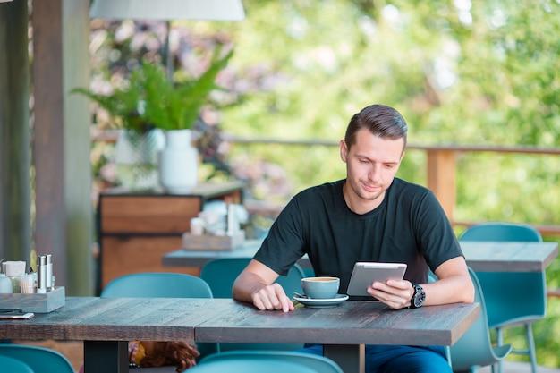 コーヒーを飲みながらの屋外カフェでラップトップを持つ若者。モバイルスマートフォンを使用している人。 Premium写真