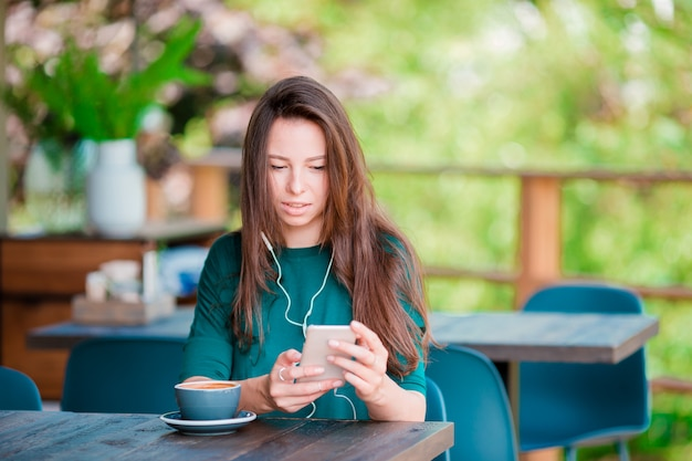 自由時間中にコーヒーショップで一人で座っている間スマートフォンを持つ若い女性 Premium写真
