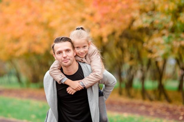 父と晴れた秋の日に屋外で彼の愛らしい小さな娘 Premium写真