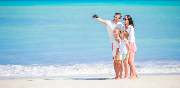 ビーチで幸せな美しい家族のパノラマ Premium写真