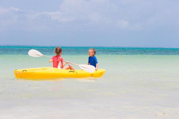 黄色のカヤックでカヤックを楽しんでいるかわいい女の子 Premium写真