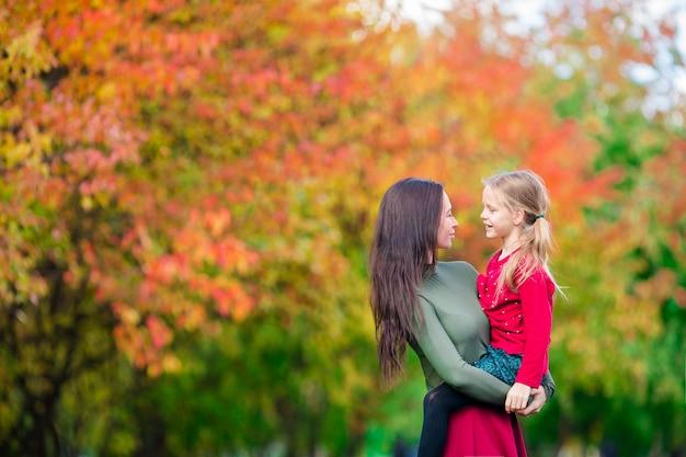 秋の日に公園で屋外の母親と子供の家族 Premium写真