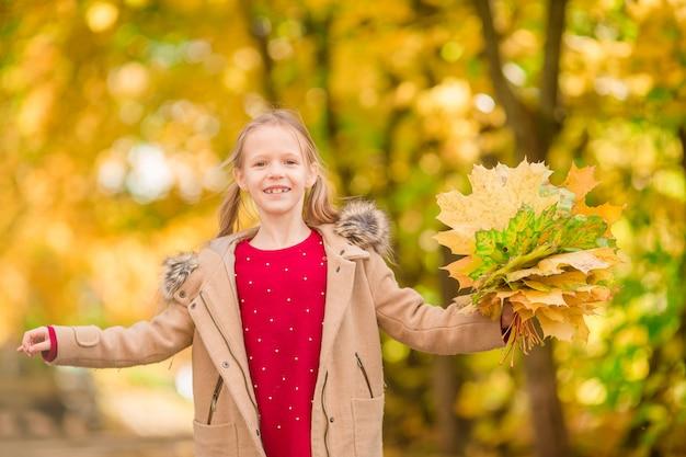 秋に黄色の葉の愛らしい少女の肖像画 Premium写真