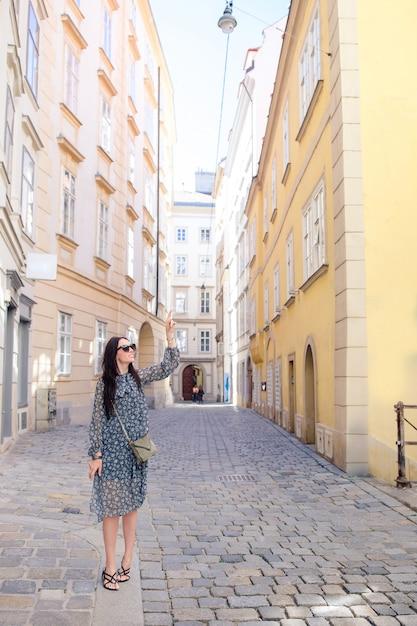 街を歩いている女性。ヨーロッパの都市で屋外の若い魅力的な観光客 Premium写真