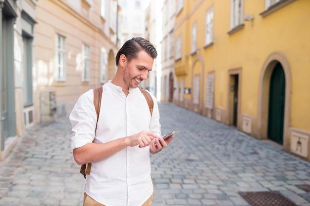 ヨーロッパ通りのバックパックで男観光客。ヨーロッパの都市の地図を探している白人の少年。 Premium写真