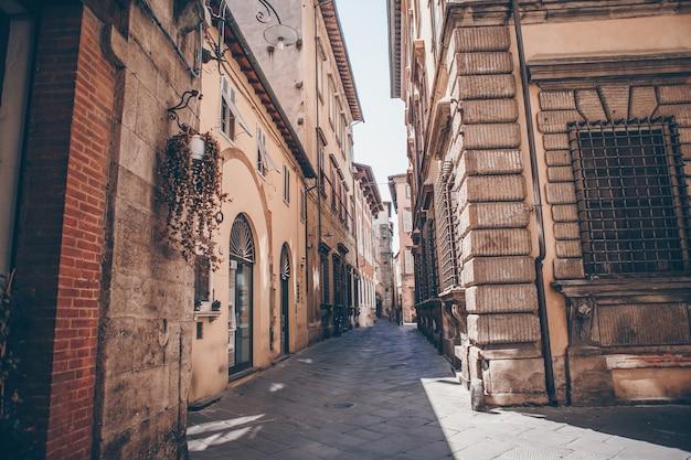 Старые красивые пустые узкие улочки в маленьком городе лукка в италии Premium Фотографии