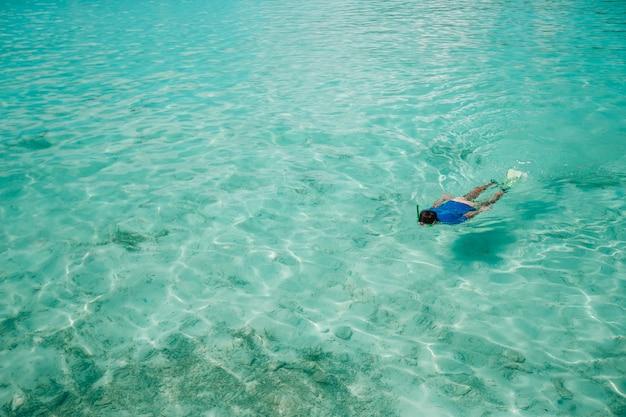 驚くほどターコイズブルーの海で泳いでいる人 Premium写真