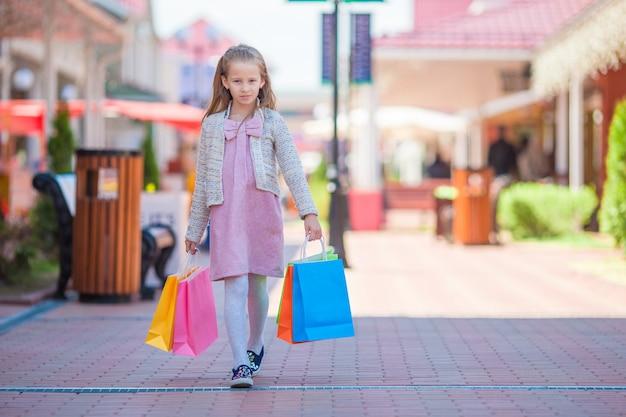 屋外の街を歩いて買い物袋を持つ愛らしい少女 Premium写真