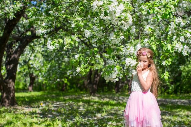 晴れた日に開花のリンゴ園でのかわいい女の子 Premium写真