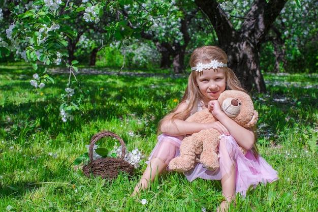 愛らしい少女は開花のリンゴ園で楽しい時を過す Premium写真