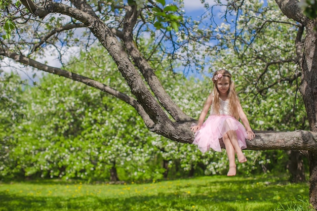 開花のリンゴの木の上に座ってかわいい女の子 Premium写真