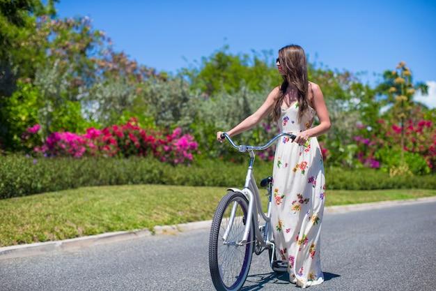 トロピカルリゾートで自転車に乗る少女 Premium写真