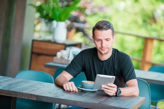 コーヒーを飲みながらの屋外カフェでラップトップを持つ若者。モバイルのスマートフォンを使用している人。 Premium写真