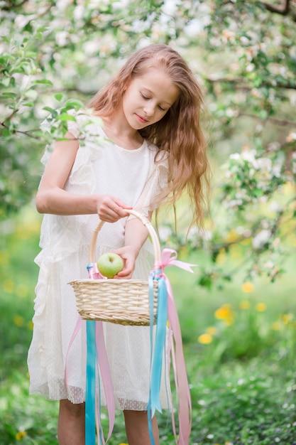美しい春の日に咲くリンゴ園でのかわいい女の子 Premium写真