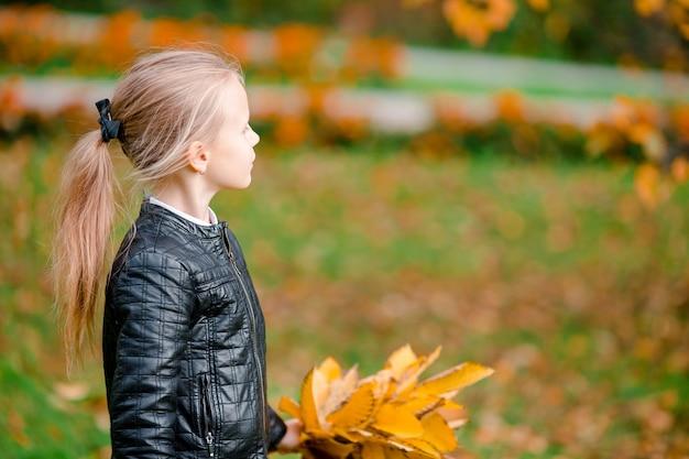 スクーターに落ちる黄色の葉の花束と愛らしい少女の肖像画 Premium写真