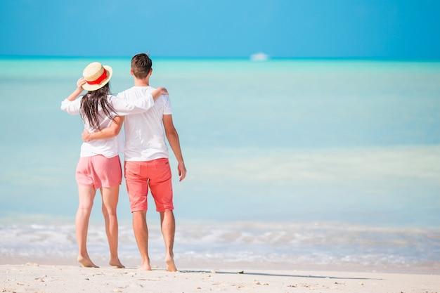白いビーチで若いカップル。新婚旅行での幸せな家族 Premium写真