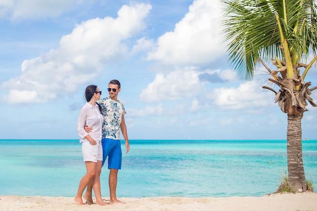 ビーチの上を歩くと夏休みを楽しんでいる素敵なカップル Premium写真