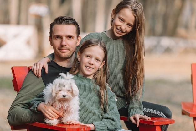 母と娘が屋外で犬と遊ぶ Premium写真