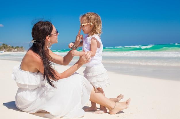 トゥルム、メキシコの白い砂浜で若い母親と楽しんでのかわいい女の子 Premium写真