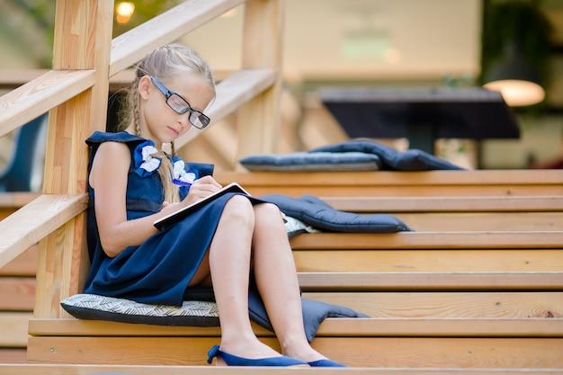 Прелестная маленькая школьница с примечаниями и карандашами напольными. обратно в школу. Premium Фотографии
