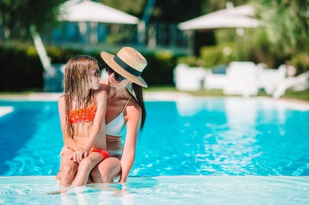 豪華なスイミングプールで夏休みを楽しんでいる家族 Premium写真