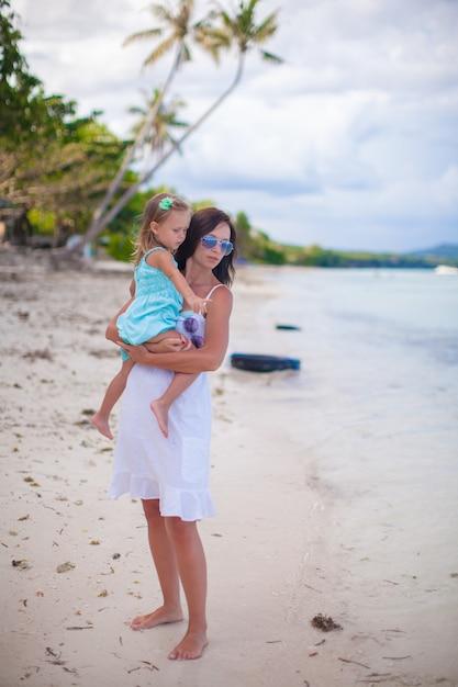 若い母親と彼女の小さな娘がビーチでの休暇を楽しんで Premium写真