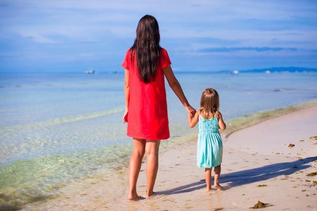 母と海を見て彼女の小さな娘の背面図 Premium写真