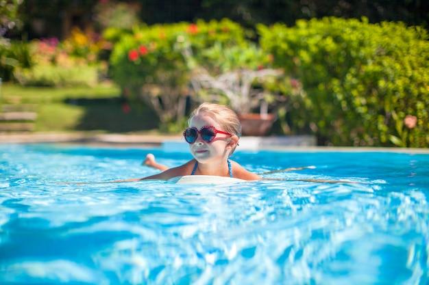 愛らしい幸せな少女は、スイミングプールで泳ぐ Premium写真