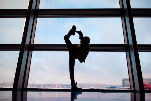 Маленькая девочка в аэропорту возле большого окна в ожидании посадки Premium Фотографии