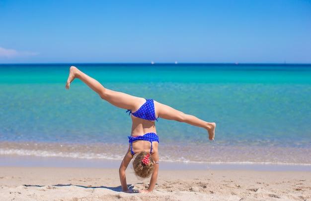 熱帯白い砂浜でホイールを作る愛らしい少女 Premium写真