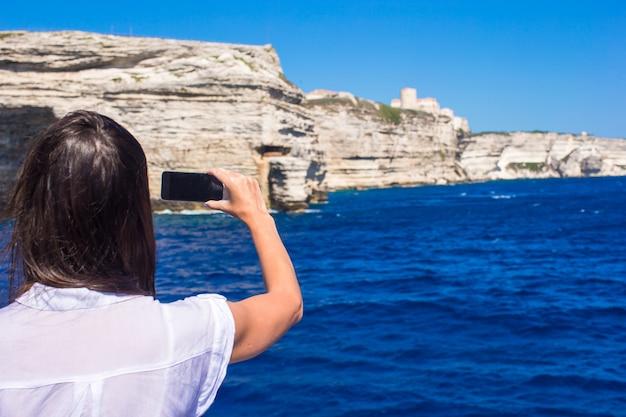 ボニファシオ、コルシカ島、フランスの携帯電話で写真を撮る女の子 Premium写真