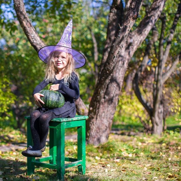 ハロウィーンの魔女の衣装でのかわいい女の子 Premium写真