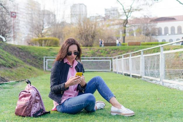 路上で屋外の携帯電話を持つ女性。女性が携帯のスマートフォンを使用しています。 Premium写真