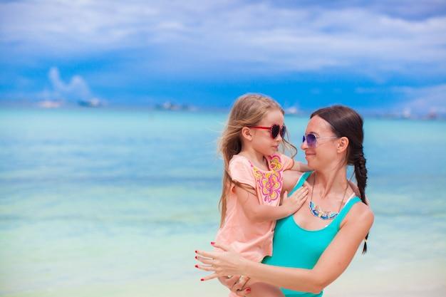 クローズアップ少女とビーチでお互いを見ている若い母親 Premium写真