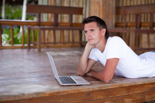 エキゾチックなリゾートでタブレットコンピューターを使用している人の肖像画 Premium写真